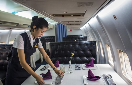 """WUHAN, CHINA - SEPTEMBER 09: The waiter clears the tableware in airplane restaurant on September 9, 2016 in Wuhan, Hubei province, China.. Different from the past airplane theme restaurants, this international route cuisine restaurant named """" jasmine aviation"""" is transformed from a retired Boeing 737 aircraft, and is the first airplane restaurant in the country. The operator of this restaurant Lilang claims that the retired aircraft was bought from the Batavia Airway of Indonesia, and it took almost 4 months in transporting and took 35 million Yuan. (Photo by Wang HE/Getty Images)"""