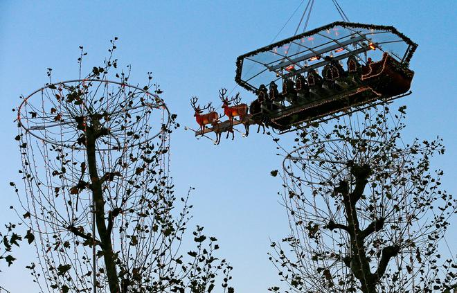 """Guests enjoy dinner at the table """"Santa in the sky"""", lifted by a crane and decorated to match the appearance of a """"Santa Sleigh"""" as part as the Christmas festivities, in Brussels, Belgium, November 25, 2016. Picture taken November 25, 2016.   REUTERS/Yves Herman"""