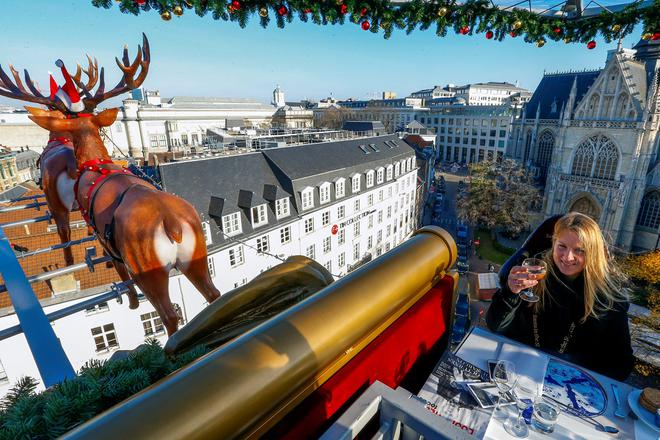 """A guest enjoys dinner at the table """"Santa in the sky"""", lifted by a crane and decorated to match the appearance of a """"Santa Sleigh"""" as part as the Christmas festivities, in Brussels, Belgium, November 25, 2016. Picture taken November 25, 2016.   REUTERS/Yves Herman"""